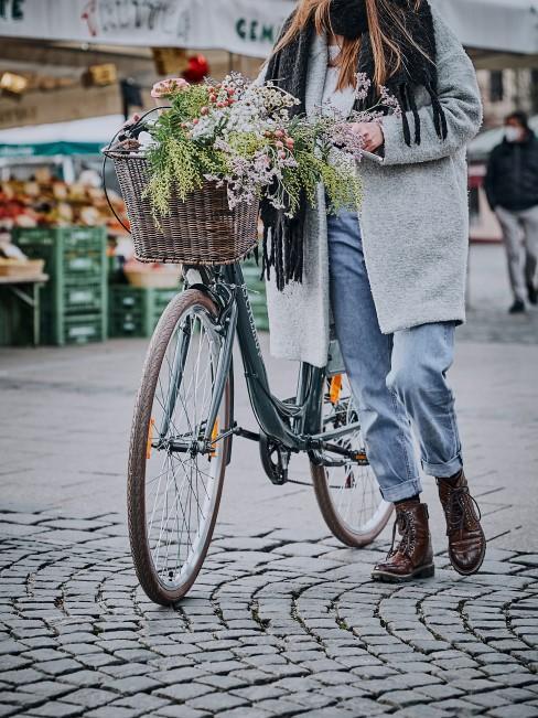 Frau schiebt ihr Fahrrad durch die Fußgängerzone