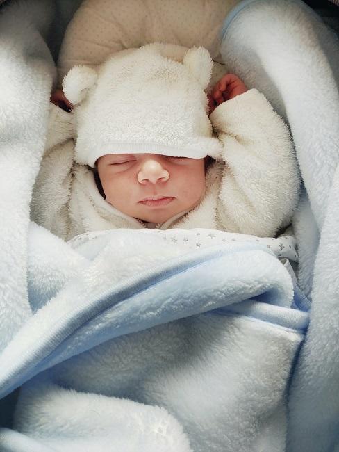 Kind eingewickelt in Decke