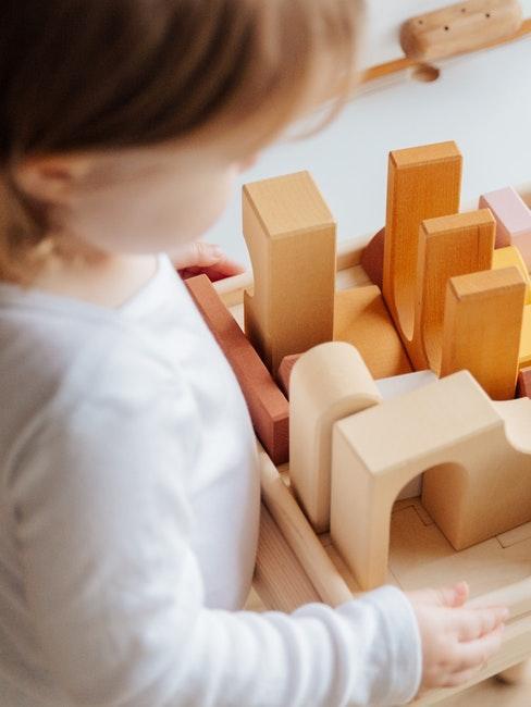 Kind spielt mit Bauklötzen aus Holz
