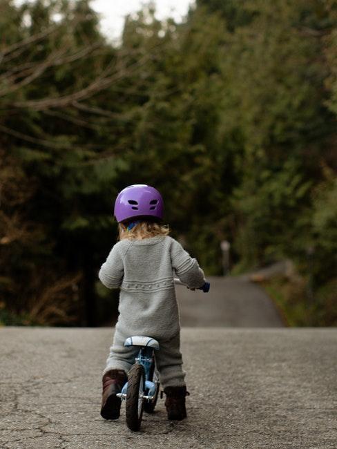 Kind fährt auf einem Laufrad in der Natur
