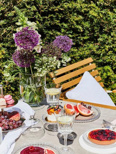 Gartentisch mit Blumen und Geschirr