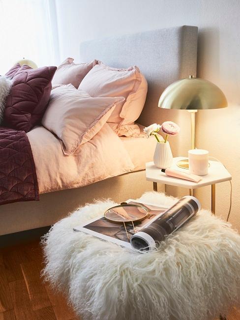 Bett mit rosa und lila Kissenbezüge neben Hocker mit Fell