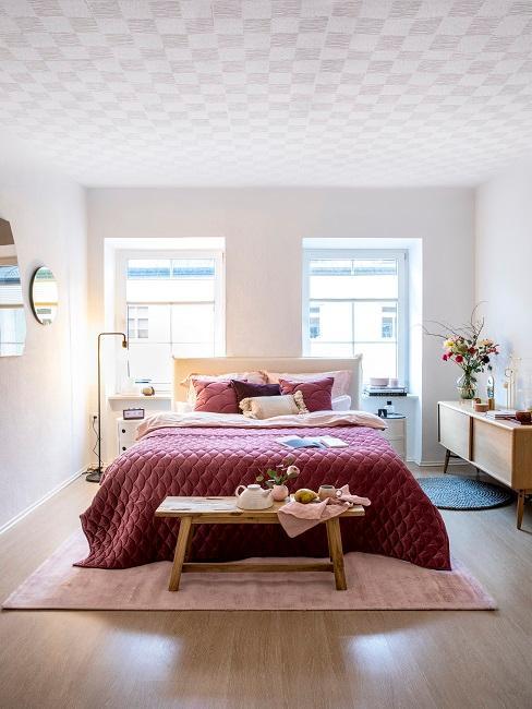 Bett mit lila Bettwäsche in hellem Schlafzimmer