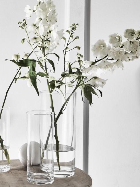 Glasvase mit Fruehlingsblumen auf Tisch