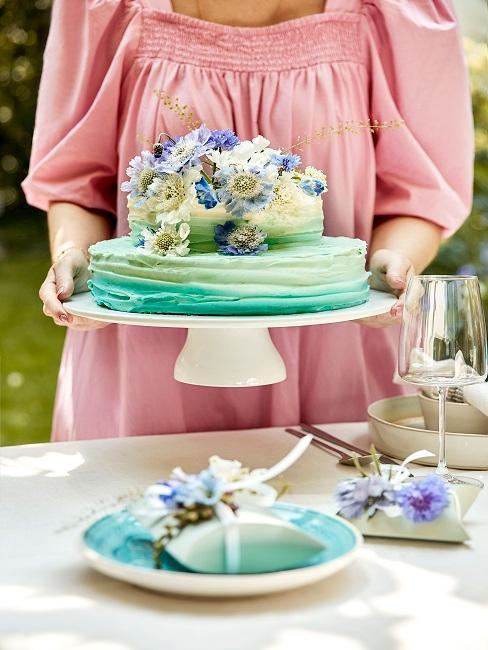 Frau in Rosa Kleid trägt Kuchen