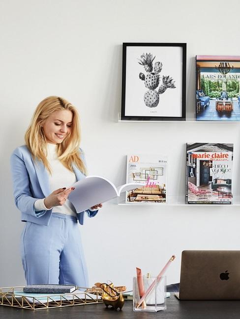 Frau steht in Büro und ließt Magazin