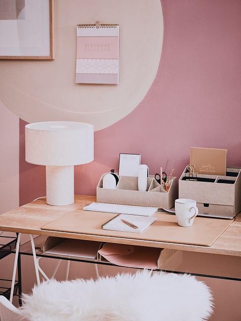 Aufgeräumter und gut organisierter Schreibtisch vor rosa Wand