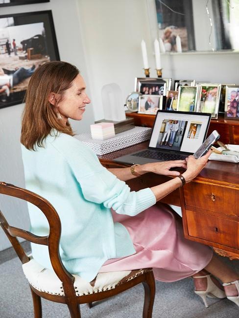Frau sitzt an Schreibtisch mit vielen privaten Fotos