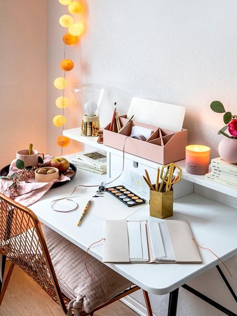 Schreibtisch mit Büroutensilien und Lichterkette