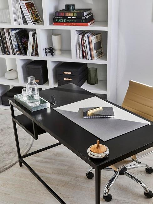 Schreibtisch in Schwarz aufgeräumt und mit Deko