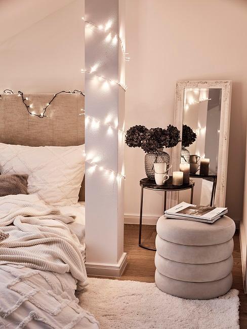 Pouf in Beige neben Bett in Beige und Lichterkette