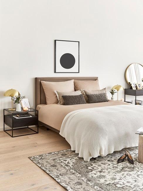 Bett mit beiger Bettwäsche in großem Schlafzimmer