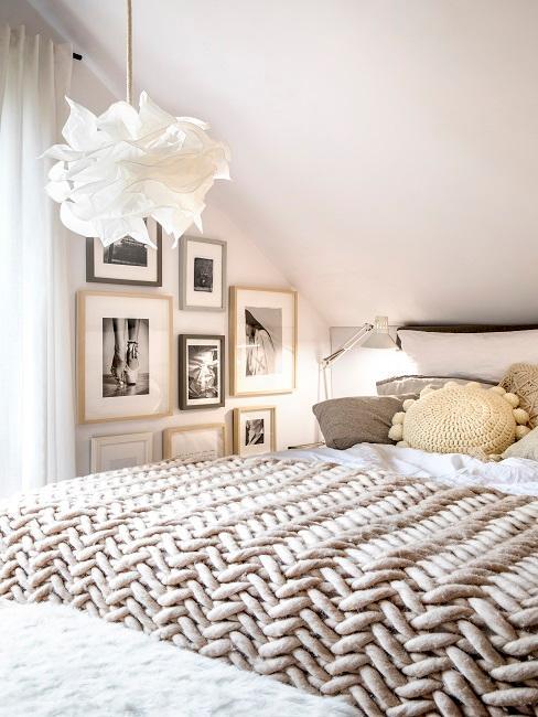 Bett mit beiger Tagesdecke und Kissen neben Fotowand