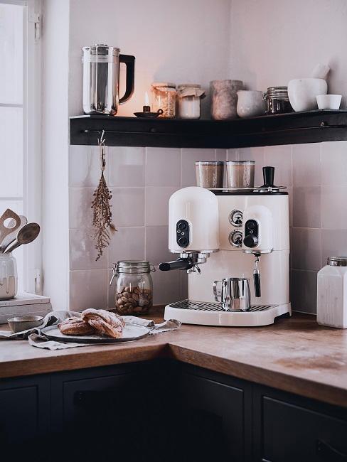 Weiße Kaffeemaschine unter Küchenregal mit Deko