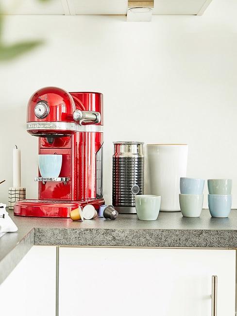 Rote Kaffeemaschine mit bunten Kaffeetassen