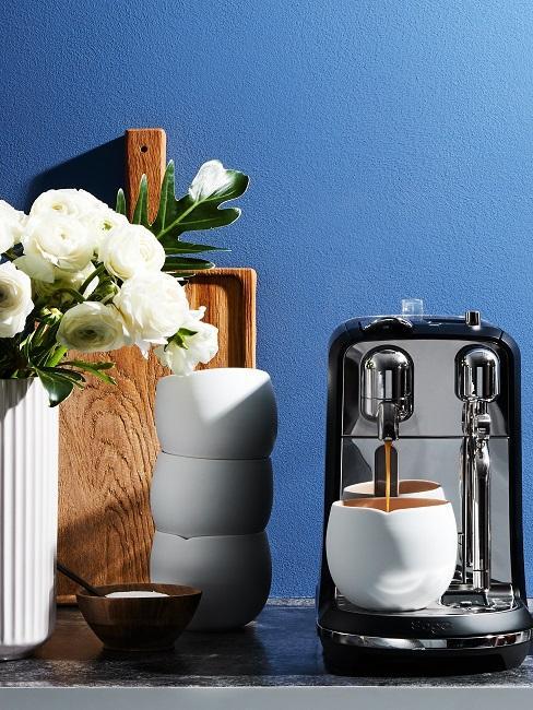 Kaffeemaschine mit weißen Kaffeebechern vor blauer Wand