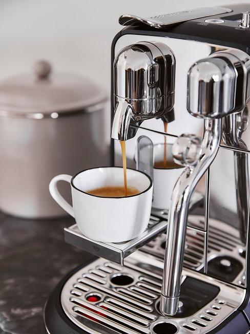 Kaffee fließt aus Kaffeemaschine in weiße Tasse