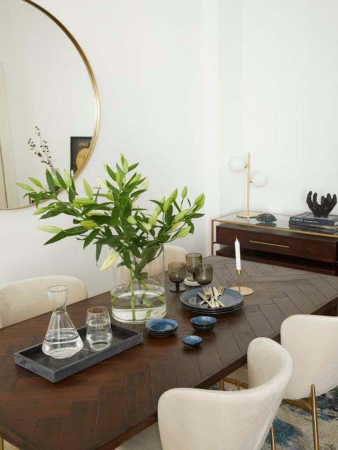 Holz-Esstisch mit Deko und Geschirr und hellen Samtstühlen