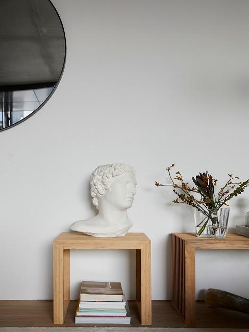 Deko-Objekt und Blumen vor weißer Wand