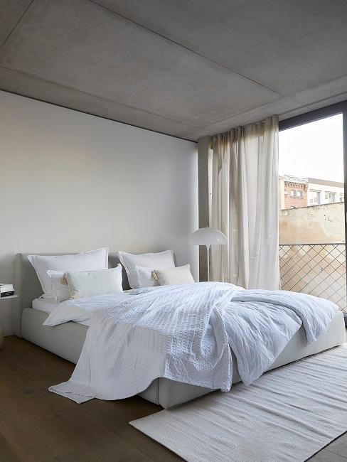 Schlafzimmer mit Bett und weißer Bettwäsche