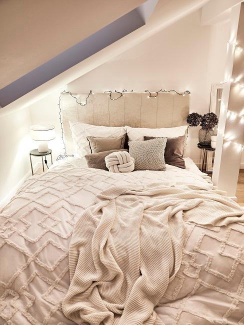 Bett mit beiger Bettwäsche und Lichterkette
