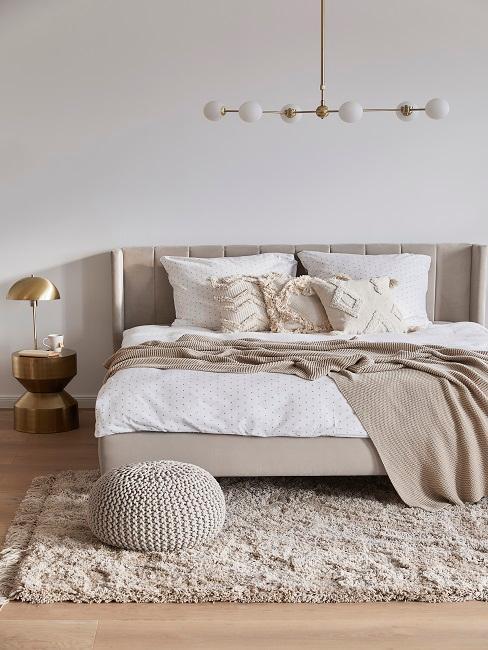 Schlafzimmer mit Doppelbett, beiger Tagesdecke, Teppich und Pouf
