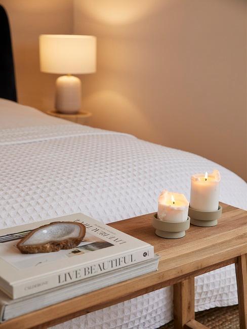 Zwei brennende Kerzen und zwei Coffee Table Books auf Bettbank
