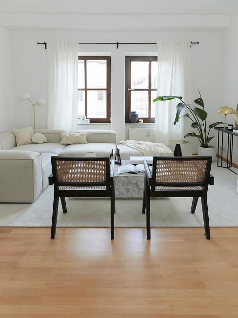 Wohnzimmer eingerichtet in hellen Farben und zwei dunklen Stühlen