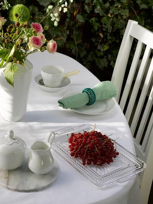 Gedeckter Gartentisch mit Blumen und Teeservice