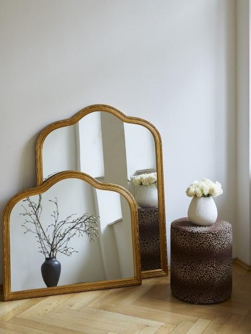 Zwei goldene Barock-Spiegel stehen auf dem Parkettboden