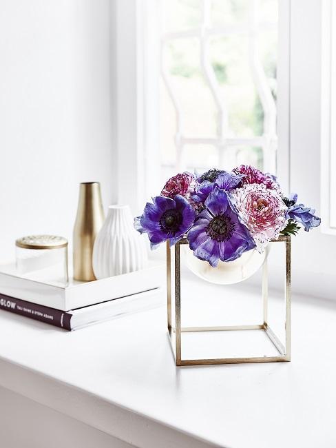 Lila Blumen in goldener Schale
