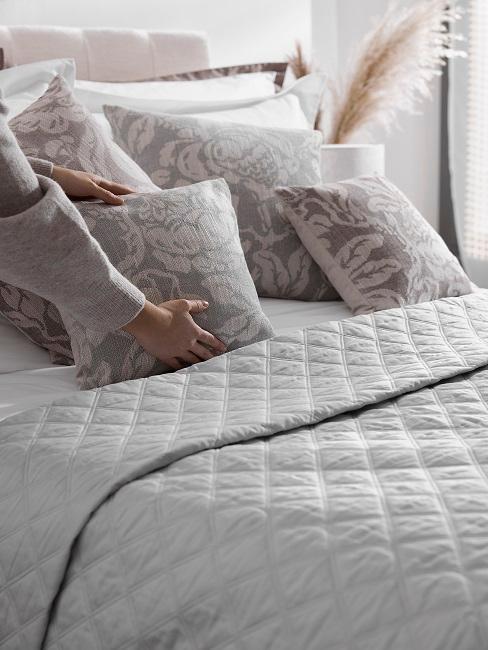Frau richtet Dekokissen auf Bett