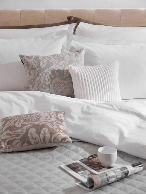 Offene Zeitschrift mit Tasse auf Bett