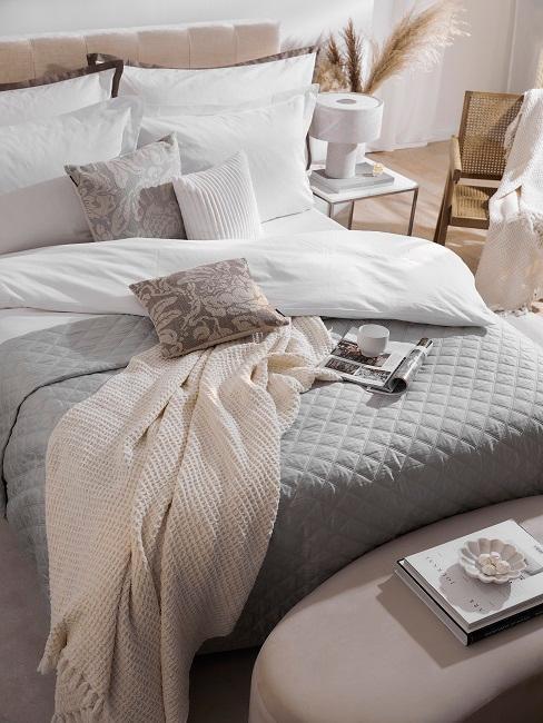 Offene Zeitschrift mit Kaffeetasse und Kissen auf Bett