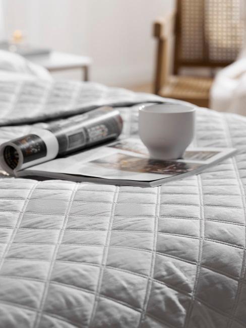 Zeitschrift auf Bett mit Kaffeetasse