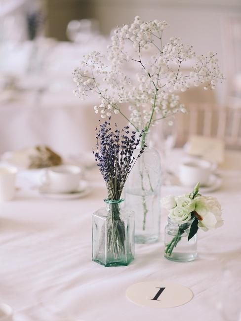 Tischnummer neben Blumen in Glasvasen