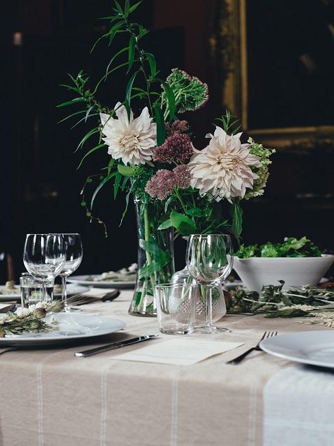 Tischkarte neben Geschirr und Blumen