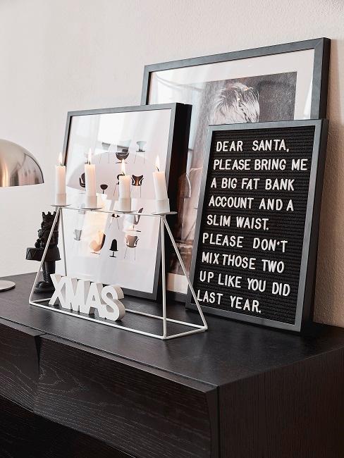 Pinboard mit Weihnachtsspruch auf schwarzem Sideboard