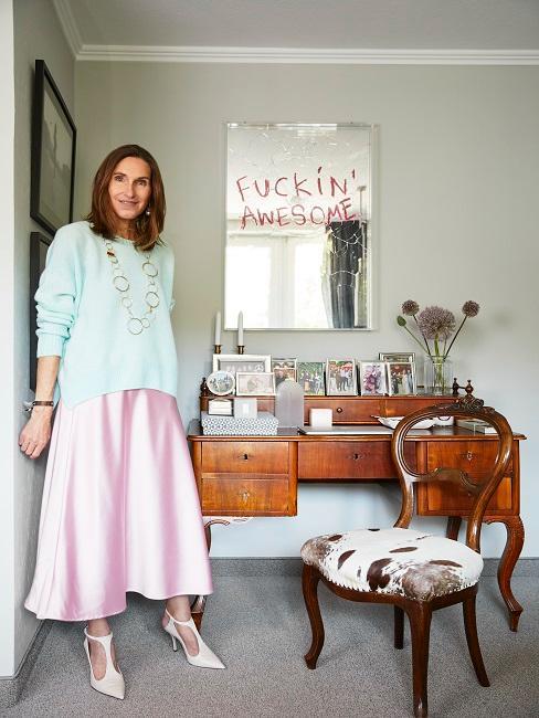 Frau steht neben Spiegel mit Spruch geschrieben mit Lippenstift