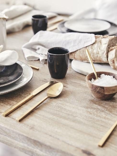 Schlichte Tischdeko mit goldenem Besteck als Blickfang