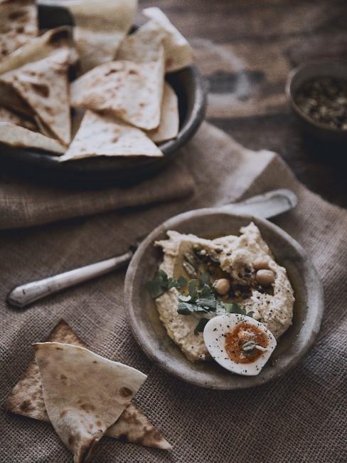 Hummus und Brot in Keramikschalen