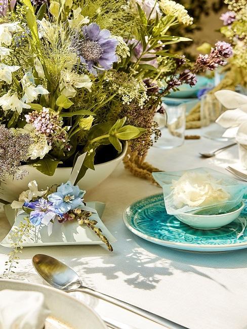 Blaue Tischdeko und Blumen