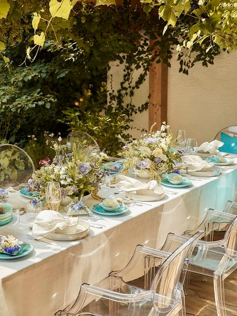 Gedeckter Tisch mit Blumen und blauem Geschirr