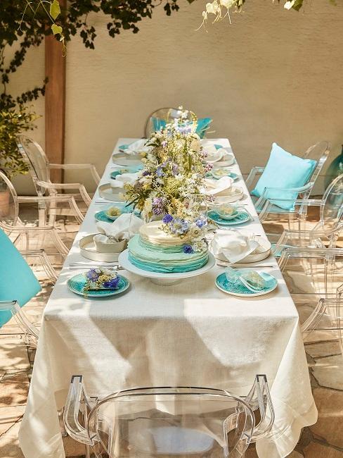 Gedeckter Tisch im Garten mit blauem Geschirr