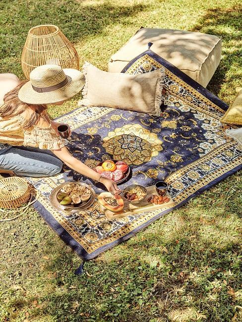 Picknick im Garten angerichtet mit Teppich und Bodenkissen