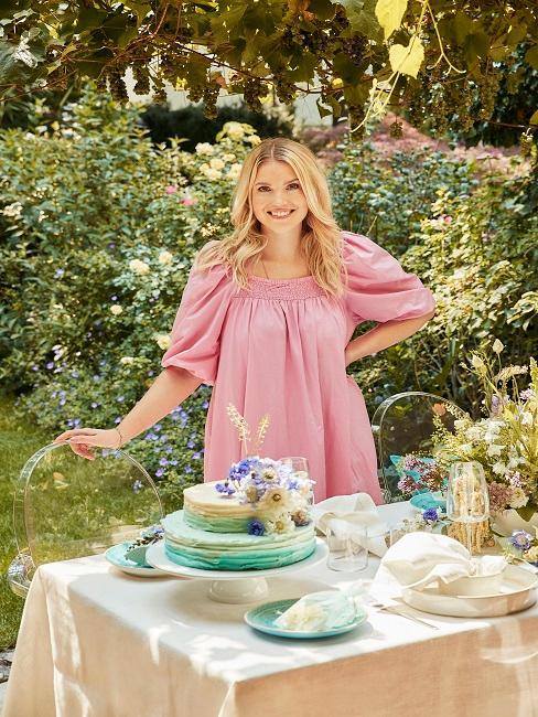 Frau steht im Garten mit gedecktem Tisch