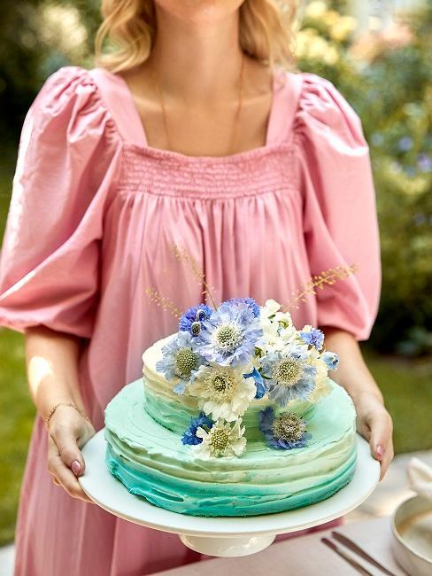Frau hält blaue zweistöckige Torte mit Blumenverzierung