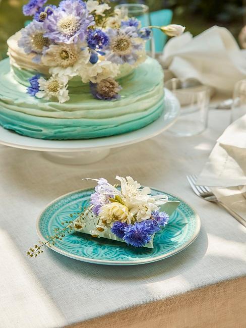 Blaue Torte auf blauem Teller und Blumendeko