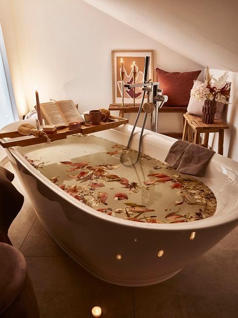 Badewanne gefüllt mit Wasser und Blüten