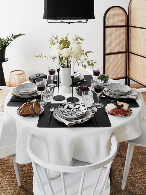 Gedeckter runder Esstisch mit weißen Stühlen